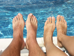 clear nails on man and woman's feet over pool